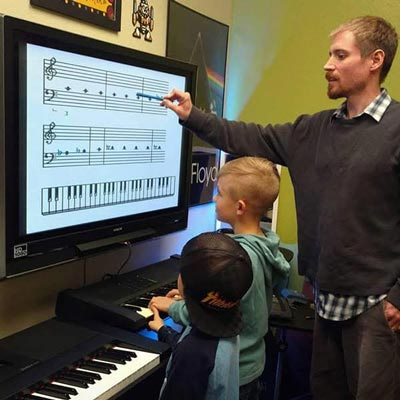 guitar and bass teacher uses nintendo screen to teach young students music theory