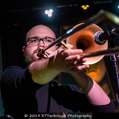 man plays trombone in live concert