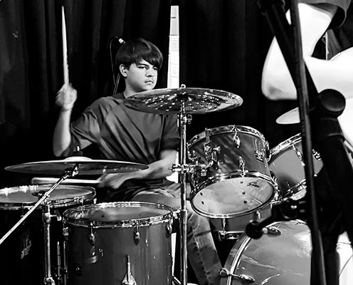 student behind drum set at recital