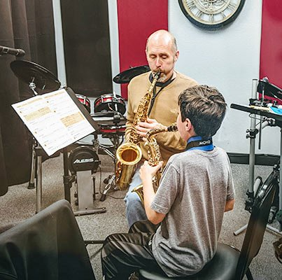 Teacher and student play saxophones in teaching room